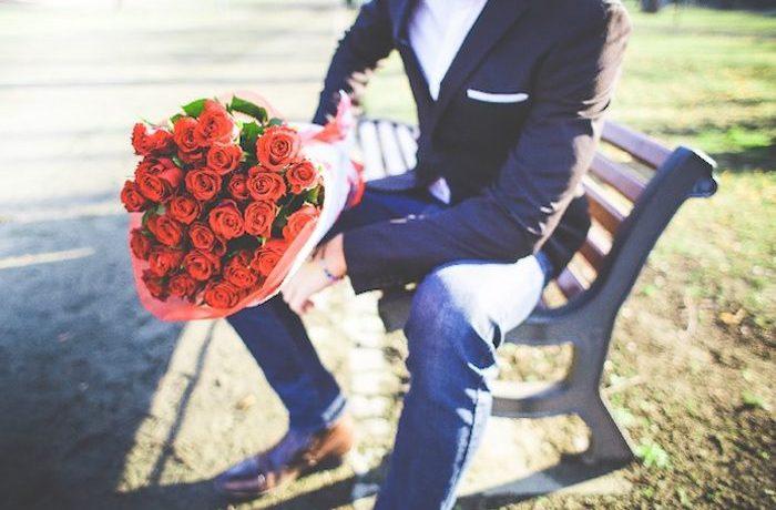 バラを持った男性がこっちを向いてベンチに座っている画像