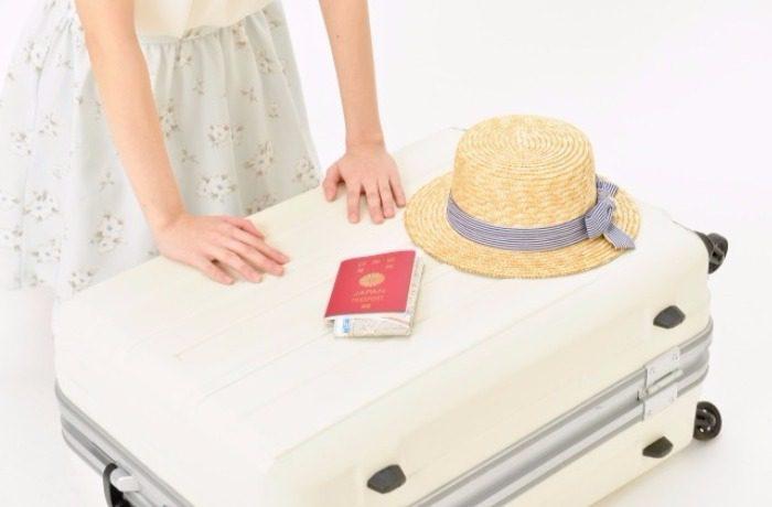 旅行の準備のキャリーケースと帽子